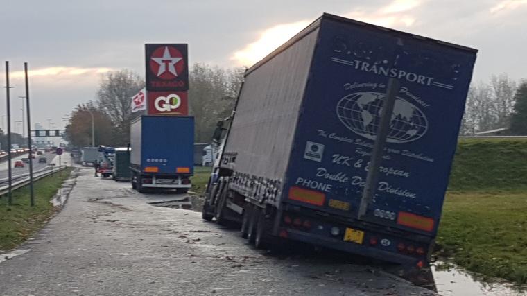 Foto Vastgereden en gekantelde vrachtwagen